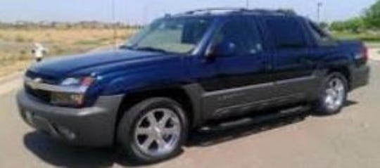 A stock photo of a dark blue Chevy Avalanche, believed to be the type of vehicle Jesse Sierra and Ester Wolfe may be traveling in.