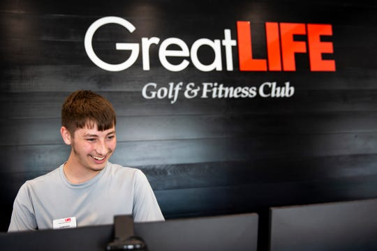 GreatLife Fitness employee Cameron Rhode greets people at the front desk, Wednesday, July 17.