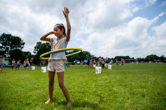 Sage Poorbear, 8, hula hoops with friends during the Hydrant Block Party in Hayward Park, Thursday, July 18.