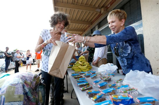 Diane Kent with Gathering Friends helps Janetta Stevens load a bag with food outside The Connecting Grounds church on Commercial Street on Tuesday, July 16, 2019.