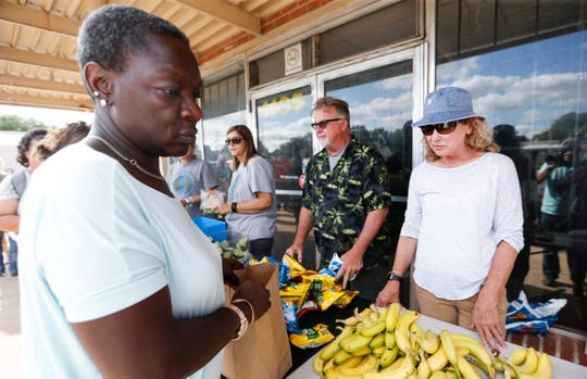Natalie Armstrong picks up food from Gathering Friends as they serve dinner outside The Connecting Grounds church on Commercial Street on Tuesday, July 16, 2019.