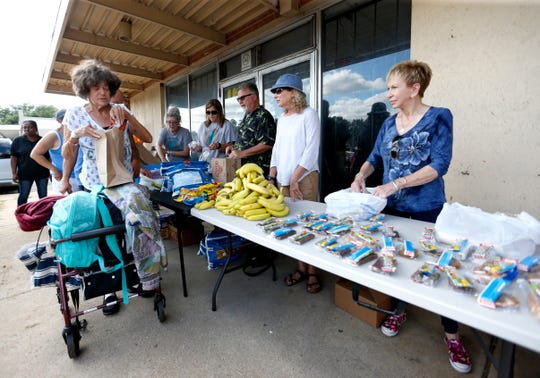 Janetta Stevens picks up food from Gathering Friends as they serve dinner outside The Connecting Grounds church on Commercial Street on Tuesday, July 16, 2019.