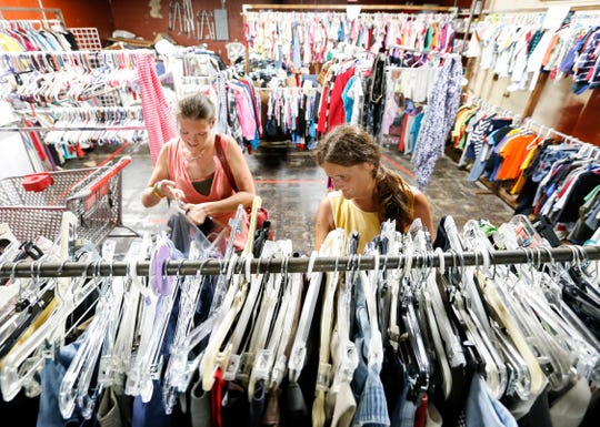Eden Williams (left) and Shawna Ince browse clothes in the clothing pantry at The Connecting Grounds church on Commercial Street on Tuesday, July 16, 2019.