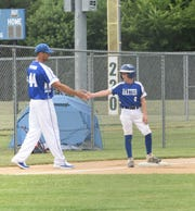 Jayden Barnum high fives his coach Jeremiah Piepkorn before scoring a run in the first inning at the 2019 Cal Ripken Baseball Midwest Plains 11U Regional, Thursday, July 18, 2019 at the Waite Park Baseball Complex.