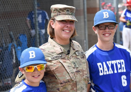 Amy Barnum, center, smiles after being reunited with her two sons, Jayden, 11, and Collin, 9, for the first time following her latest deployment to Kuwait Thursday, July 18, 2019 at the Waite Park Baseball Complex.