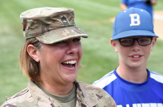 Amy Barnum, smiles after being reunited with her two sons, Jayden, 11, and Collin, 9, for the first time following her latest deployment to Kuwait Thursday, July 18, 2019 at the Waite Park Baseball Complex.