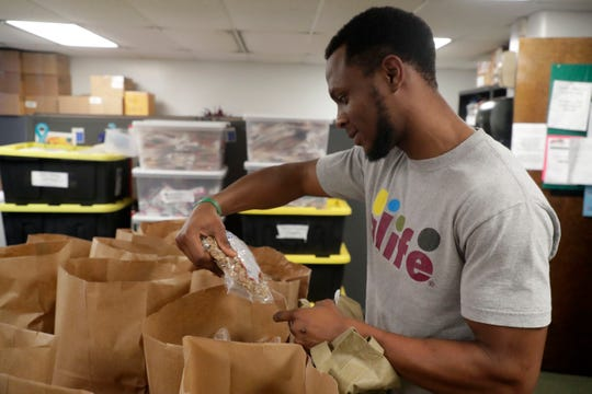 Sean Fisher, a FAMU student, sorts through the food items that he can pick from in the FAMU food pantry Thursday, July 18, 2019.