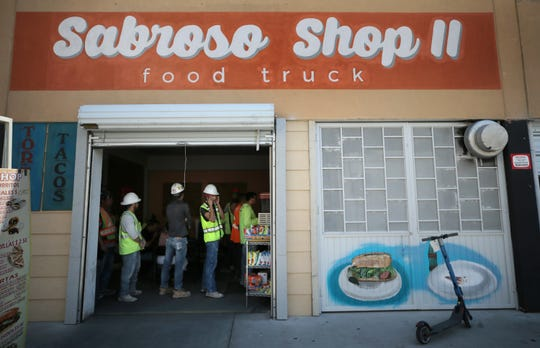 Construction workers line up at the Sabroso food truck which is tucked inside the parking garage at Santa Fe and San Antonio streets in Downtown El Paso.