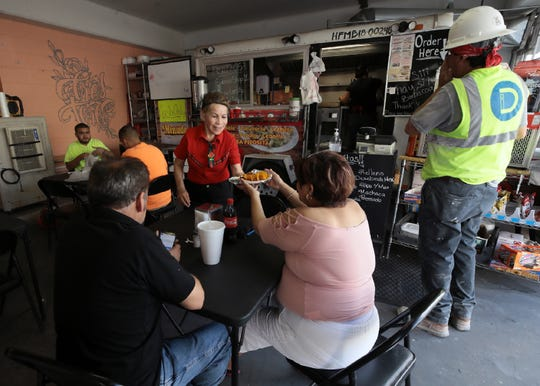 Gloria Rocha serves customers from the Sabroso food truck inside a parking garage in Downtown El Paso.