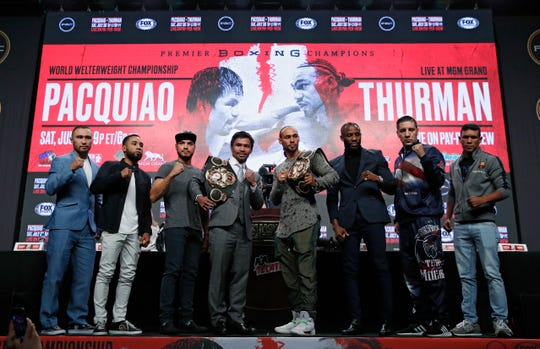 From left, Sergey Lipinets, Luis Nery, Omar Figueroa, Manny Pacquiao, Keith Thurman, Yordenis Ugas, John Molina Jr. and Juan Carlos Payano pose during a news conference Wednesday, July 17, 2019, in Las Vegas. All eight boxers are scheduled to fight Saturday in Las Vegas.