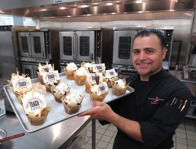 Sergio Gonzalez, pastry chef for University Auxiliary Services at CSU Channel Islands in Camarillo, poses with a tray of the elaborately decorated cupcakes he made to honor Ventura County foster youth during their TEACh Scholars awards ceremony on campus in June.