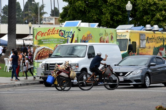 A man shuttles his belongings on his bike along Fifth Street in Downtown Oxnard on Thursday as a farmers' market takes place in Plaza Park.