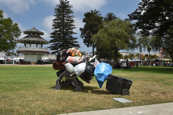 The personal belongings of a transient are packed up on a stroller as a farmers market takes place in Plaza Park in July.
