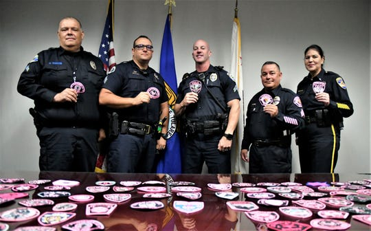 (Left to right): Porterville Cpl. Marcial Morales, Tulare Sgt. Lonzo Anderson, Visalia Agent Kevin Grant, Farmersville Sgt. Rafael Vasquez-Perez, Exeter Lt. Liz Yarber pose with their department's pink patches on Thursday, July 18, 2019.