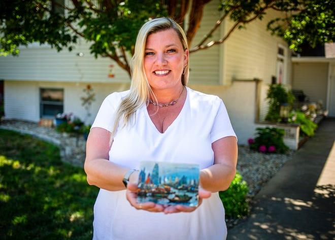 "Kim Draper received a postcard at her home in Springfield on July 8, 2019 that was postmarked and sent from Hong Kong exactly 26 years ago on July 8, 1993 to a previous family that lived at her address. Draper is trying to track down the family that the postcard was sent to, which was addressed to Leena and Muhammad Ali Kizilbash and is signed ""See you guys soon. Your Dad."" (Justin L. Fowler/The State Journal-Register via AP)"