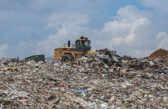 Dumps and trucks lay out layers of waste on top of the New Castle landfill in Delaware.