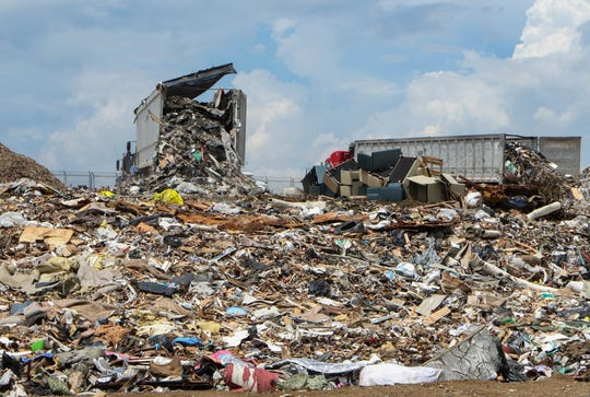 Dumps and trucks laying out layers of waste on top of the New Castle landfill in Delaware in July.
