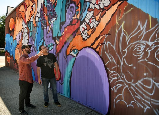 International mural artist Joerael Numina, left, talks with Jeff Marion, owner of Deviance Skate Supply, about the mural being created on the side of the business's building on Indiana.