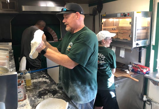 "Seymour head football coach Hugh Farmer and his wife Kari cook pizzas in their mobile ""Green Inforno"" during the spring and summer."