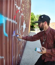International mural artist Joerael Numina works on a large piece he is creating on the south wall of Deviance Skate Supply.