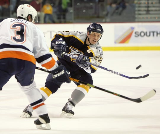 Nashville Predators center Greg Johnson (22) passes the puck past New York Islanders defenseman Brent Sopel (3).