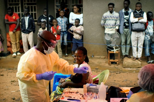 In this photo taken Saturday, July 13, 2019, a nurse vaccinates a child against Ebola in Beni, Congo, Democratic Republic of Congo. The World Health Organization has declared the Ebola outbreak an international emergency after spreading to the largest city of Congo, Goma, this week.