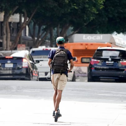 A man in downtown Los Angeles rides a scooter where he's supposed to, on the street, instead of a sidewalk