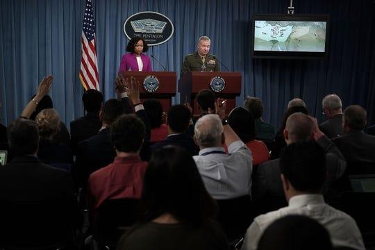 Pentagon Chief Spokesperson Dana W. White (L) and Marine Lt. Gen. Kenneth F. McKenzie Jr. (R), participate in a news briefing at the Pentagon April 14, 2018 in Arlington, Virginia.