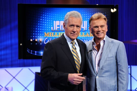 Alex Trebeck, left, and Pat Sajak pose on the set of