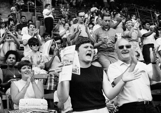 Excited fans stand and cheer when an announcement came over the public address system of a safe lunar landing for the Eagle, Apollo 11, during the Philadelphia Phillies, Chicago Cubs doubleheader baseball game, at Connie Mack Stadium, July 20, 1969, Philadelphia, PA.