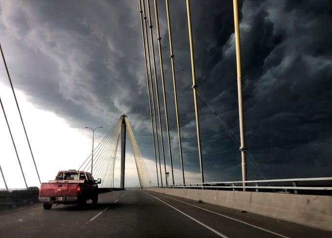 A truck drives east out of Alton, Ill., over the Clark Bridge as clouds from a severe warned thunderstorm roll in on Wednesday, July 17, 2019. The storm knocked out power to thousands of customers in St. Louis County and St. Charles County. St. Louis is under excessive heat warning until Saturday night.
