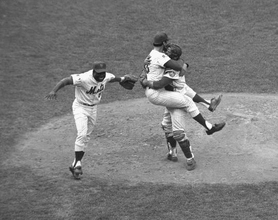 In this Oct. 16, 1969 file photo, New York Mets catcher Jerry Grote embraces pitcher Jerry Koosman as the Mets defeated the Baltimore Orioles in the fifth game to win the World Series at New York's Shea Stadium. At left is teammate Ed Charles.