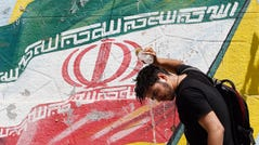 An Iranian cools off in front of a wall painting of Iran's national flag in a street of Tehran, Iran, 22 June 2019.