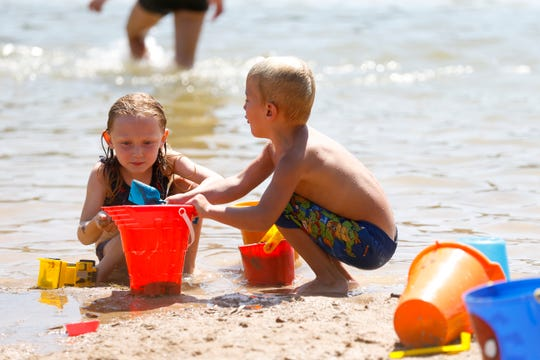 Olive Haneman (left) and Mosely St. Marie build a sandcastle at Plamann Park Lake on July 19, 2019 in Appleton, Wis.
