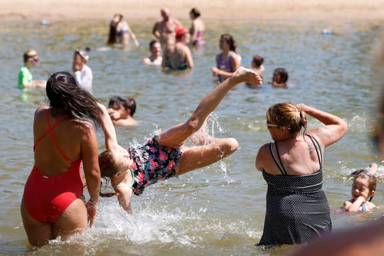 Stacy Clark (right), and Leslie Clark (left) toss MyLee Clark into the water Friday at Plamann Park Lake in Appleton as an intense heatwave hovers over the region.
