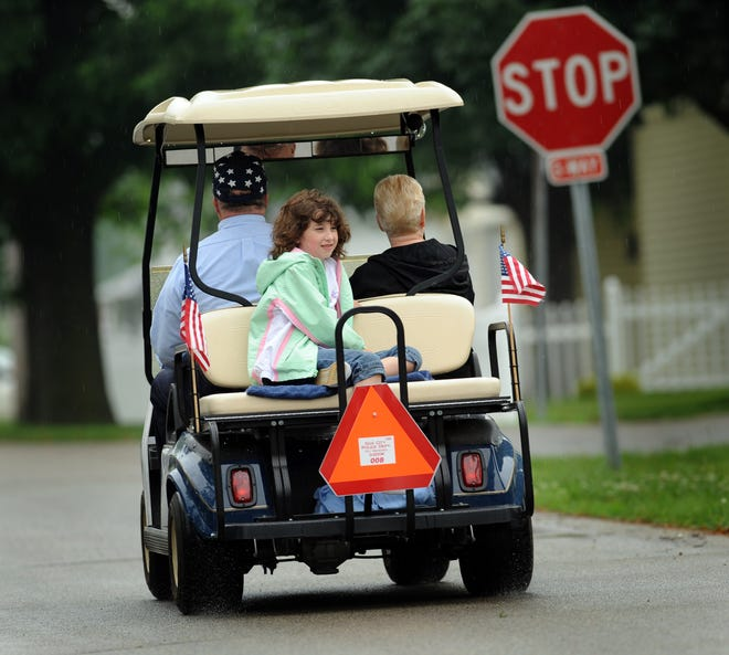Miranda Hillman rides on the back of a golf cart driven by her grandfather Larry Terwillegar in Gas City, Indiana. Terwillegar uses an electric golf cart to get around the community as an alternative to his car. Gas City has allowed golf carts on its streets since 2006.