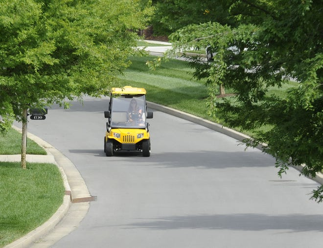 A woman drives a golf cart on a street in Franklin, Tennessee.
