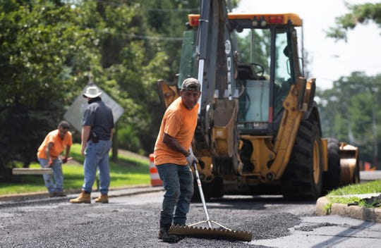 Severino Sarmieuto smooths our fresh hot macadem in spite of the heat on Friday. Workers lay new pavement at intersection of Bowne and Naomi Roads in Ocean Township.
