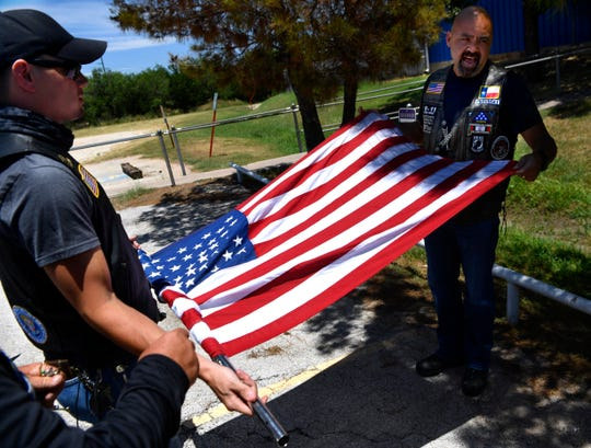 Nathaniel Gallion, (left) and Dennis Kuhn, both of Abilene, roll up the Nation of Patriots flag before taking it to the Dallas-Fort Worth area on Wednesday. The group of about 10 riders met at American Legion Post 57 and escorted the flag east to American Legion Post 453
