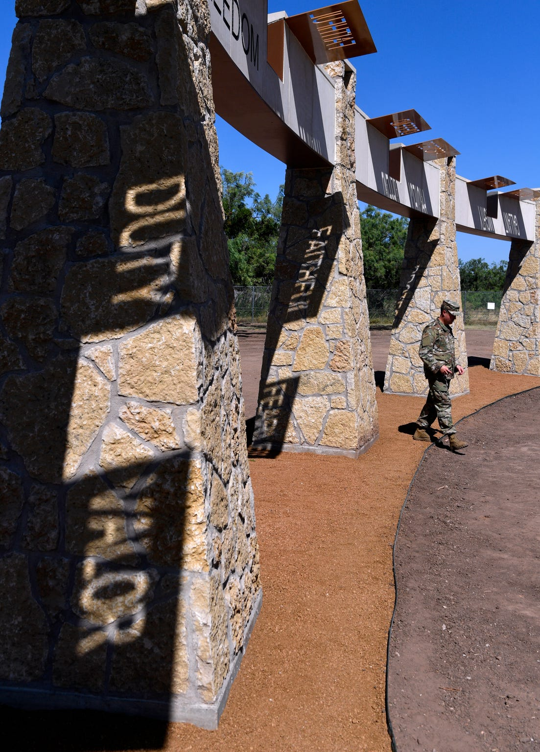 Chief Msgt. Trevor Smith of the 314th Airlift Wing in Little Rock, Ark., walks beneath the arches after the Dyess Memorial Park extension dedication July 19. A feature of the monument is the sunlight that shines through overhead metal stencils, projecting words onto the ground and rock columns below.
