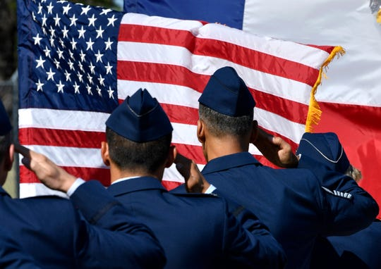 U.S. Air Force officers salute the flag during the singing of the national anthem at the start of Friday's dedication of the Dyess Memorial Park expansion.