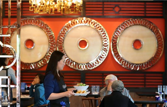 Viola Mai carries entrees to diners at Blossom Chinese Cuisine in Poulsbo on Friday.