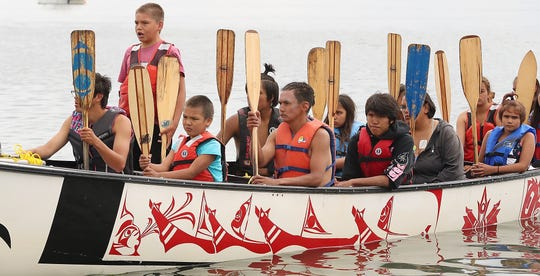 Arnie Thomas, front, stands and sings as part of the Ahousaht First Nation canoe family's greeting upon arrival to the shore at Point Julia on Thursday.