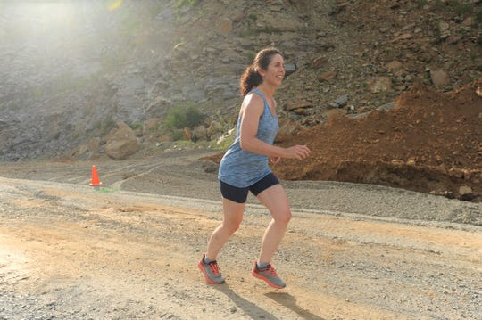Jane Dean, who will run the Asheville Sprint Spartan Race at Grove Stone & Sand on July 28, makes her way through the quarry during a practice run on July 16.