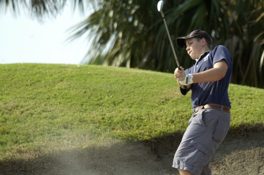 A golfer blasts out of the sand at Viera East Golf Club.