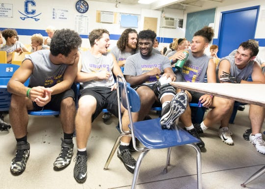 Jamarcus Carroll talks with his teammates as he rests his leg during an unexpected lightning delay in the middle of a 7-on-7 drill with the Chillicothe football team at Chillicothe's Herrnstein Field on July 18, 2019.