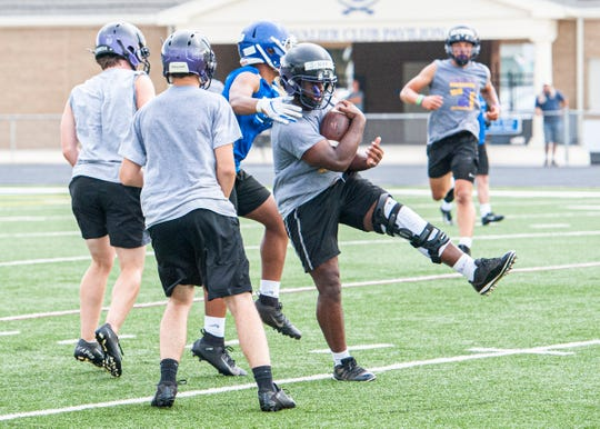 Jamarcus Carroll runs the ball after catching it during a 7-on-7 drill with the Chillicothe football team at Chillicothe's Herrnstein Field on July 18, 2019.