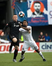 D.C. United forward Wayne Rooney (9) and FC Cincinnati defender Alvas Powell (92) compete for the ball in the first half of the MLS soccer match between FC Cincinnati and D.C. United on Thursday, July 18, 2019, in Cincinnati.