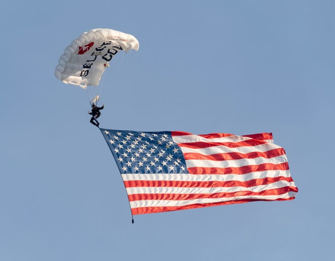 A member of FastTrax Skydivers carries the American flag into Nippert Stadium prior to the MLS soccer match between FC Cincinnati and DC United on Thursday, July 18, 2019 in Cincinnati.