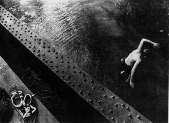 12-year-old Danny Pederson jumps off a bridge in Clive into the cool water in an image that ended up on the cover of the Des Moines Register on July 13, 1955.